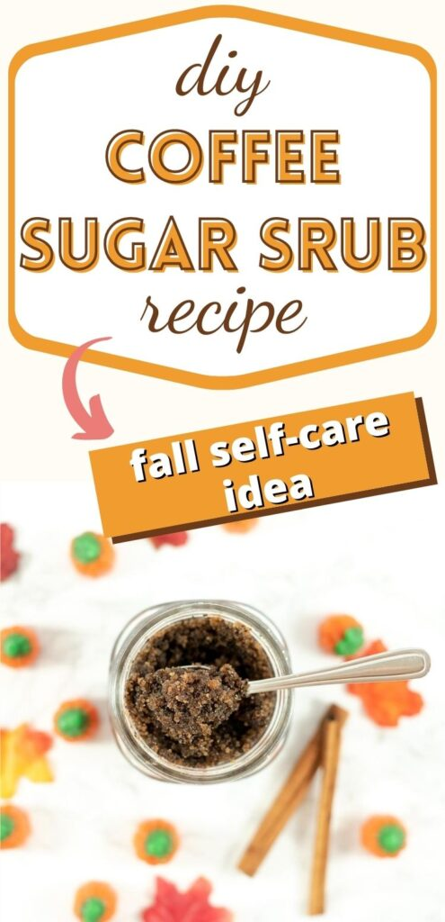 """Text """"diy coffee sugar scrub recipe - fall self-care idea"""" below the text is a jar with a coffee sugar scrub and a small metal spoon. The jar is surrounded by fall leaves, candy pumpkins, and cinnamon sticks."""