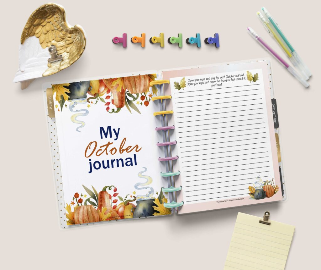"""A flat lay of an open Happy Planner Classic with a page """"My October Journal"""" with watercolor pumpkins and leaves on the left and a lined journal page on the right. There are colorful binder clips, a tray shaped like gilded wings, and three gel pens above the planner. Below the planner is a yellow note sheet with a gold binder clip."""