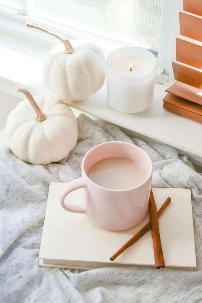 a shot of a cozy journaling scene with two white pumpkins, a lit candle on a windowsill, and a pink mug with hot chocolate resting on a white notebook
