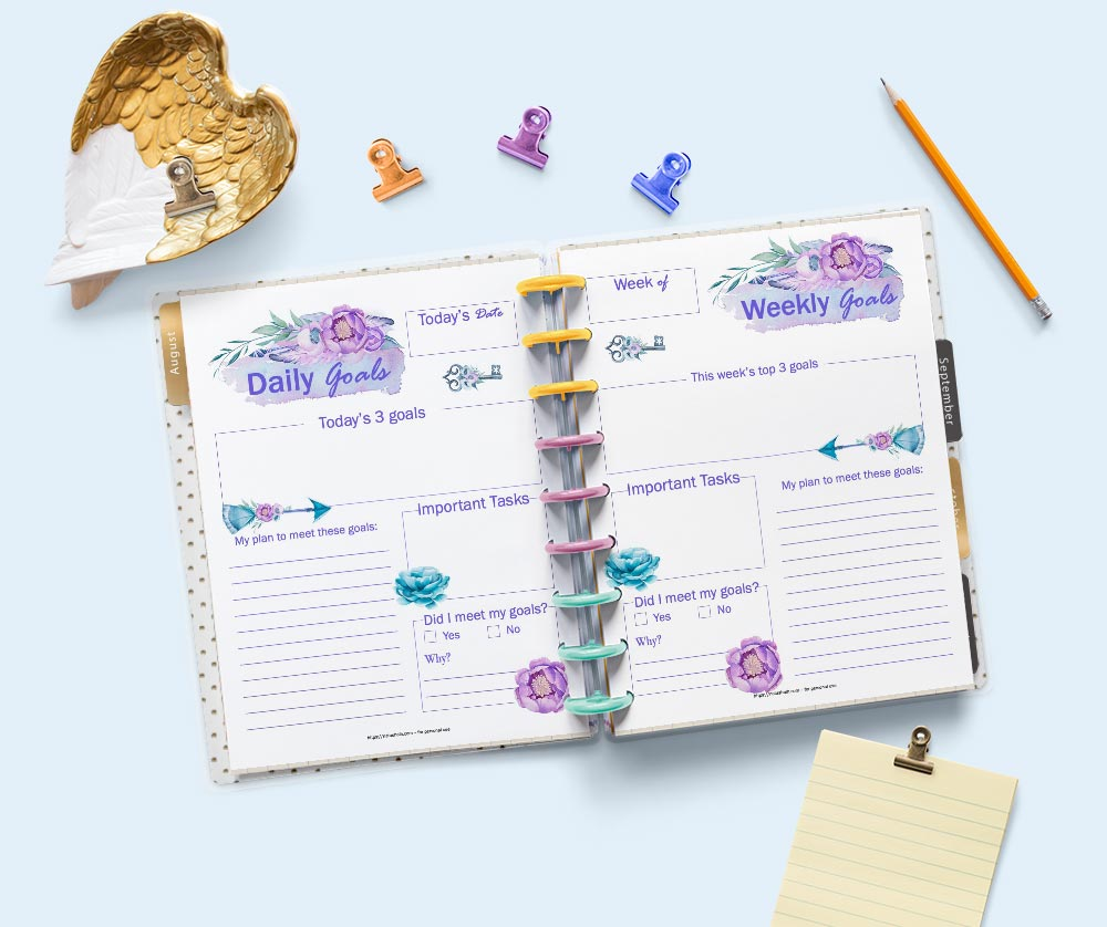 A flatly scene of a Happy Planner classic planner open to daily and weekly goal setting planner pages. The pages feature purple and pink watercolor anemone flowers and boho arrows. The planner is surrounded by stationary supplies.