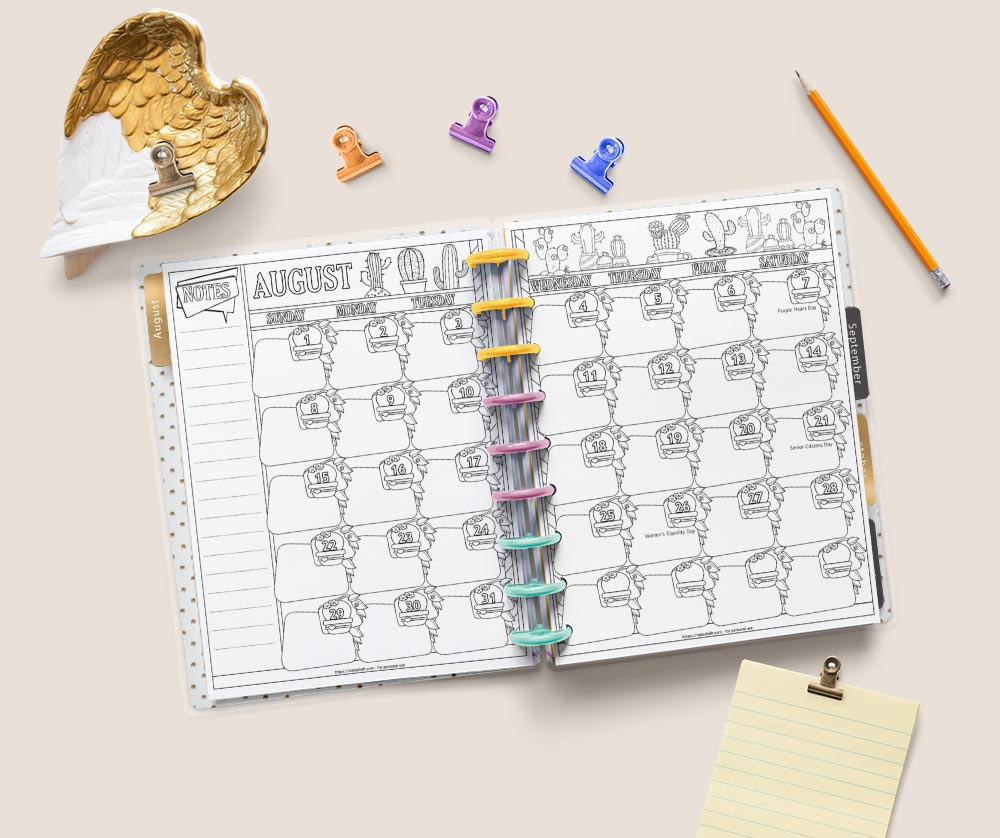 A flatly image of a Happy Planner Classic open to a double page spread for the month of August 2021. The pages have cacti to color. Around the planner are desk supplies including a yellow pad of paper, a tray shaped like feathered wings, four binder clips, and a yellow pencil.