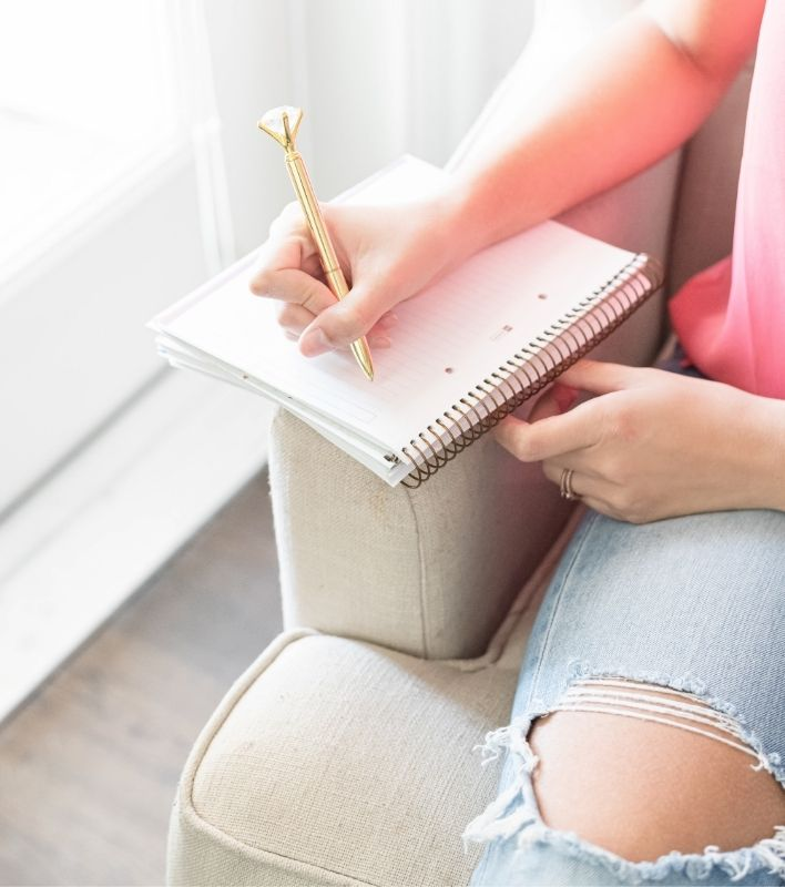 A close up picture of a woman journaling while sitting on a sofa. The woman's hands, knee, and part of her pink shirt are visible. She's holding a large gold pen and writing in a spiral notebook while leaning it on the arm of an oatmeal colored couch.