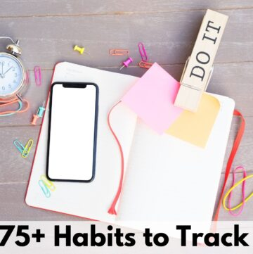 "text overlay ""75+ habits to track"" on a picture of an open blank journal with a large clip reading DO IT, a blank phone, and an assortment of rubber bands, push pins and paper clips"