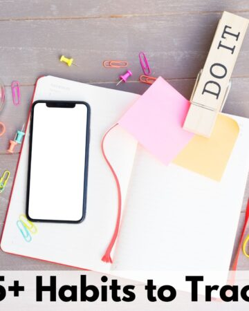 """text overlay """"75+ habits to track"""" on a picture of an open blank journal with a large clip reading DO IT, a blank phone, and an assortment of rubber bands, push pins and paper clips"""