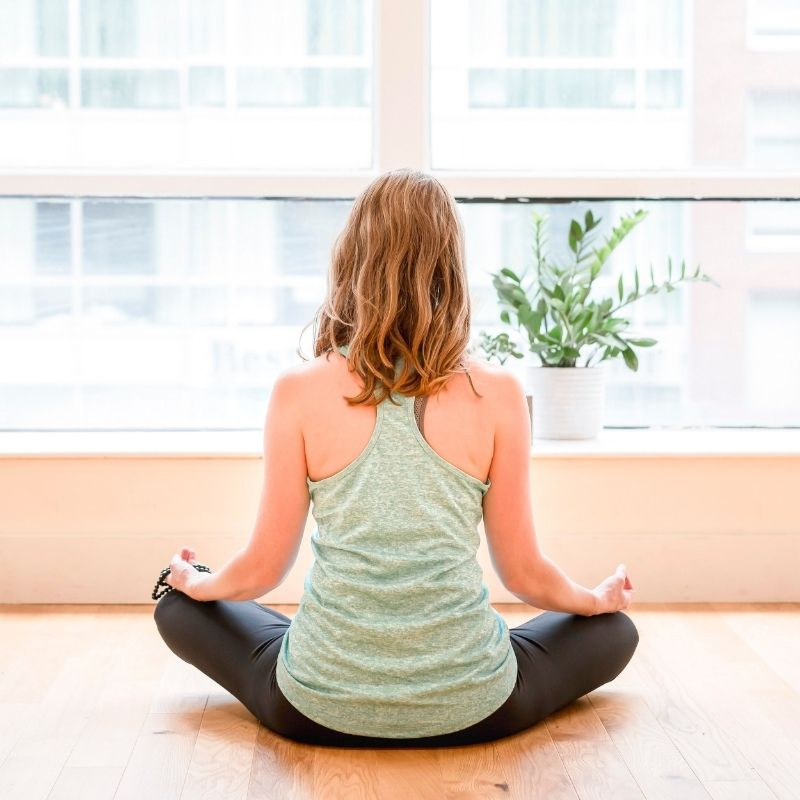 A picture of a woman sitting on a wood floor looking out a window in meditation. She is facing away from the camera and is wearing a green tank top and black yoga pants