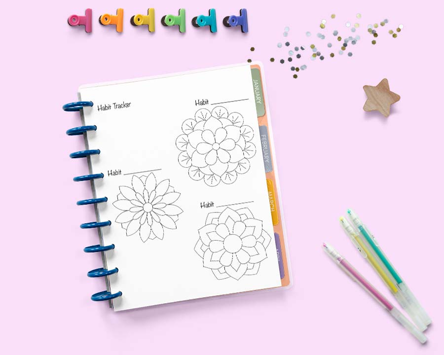 an open disk bound Happy Planner on a pink surface with colorful binder clips and gel pens. The planner is open to a page with three small circular trackers shaped like geometric flowers.
