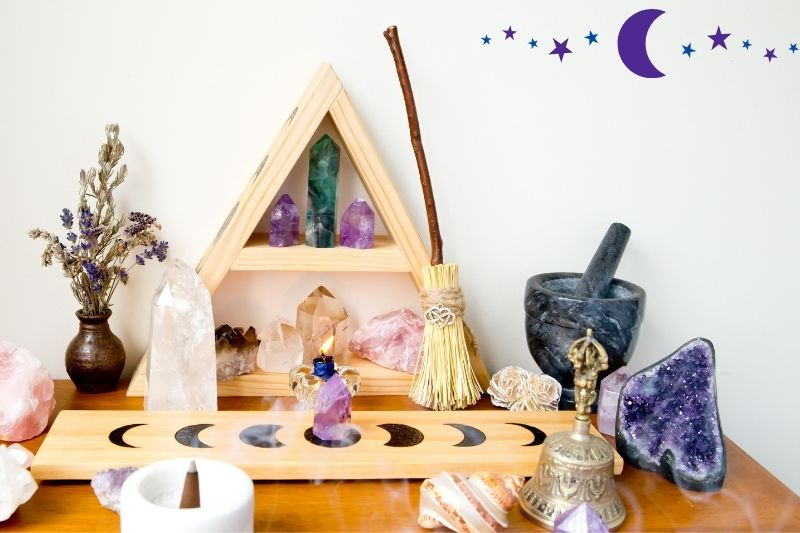 A home altar for celebrating a full moon ritual. There are candles, crystals, a bell, a shell, a burning incense cone, and a vase with dried flowers on a wood table. A triangular shelf with crystals is against the wall with a small broom.