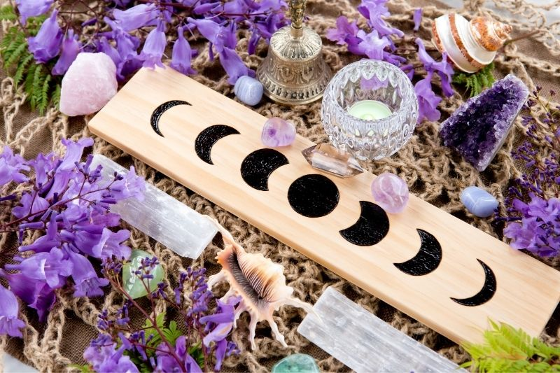 A board with the phases of the moon surrounded by purple bellflowers, two selenite wands, a candle, and amethyst crystals.