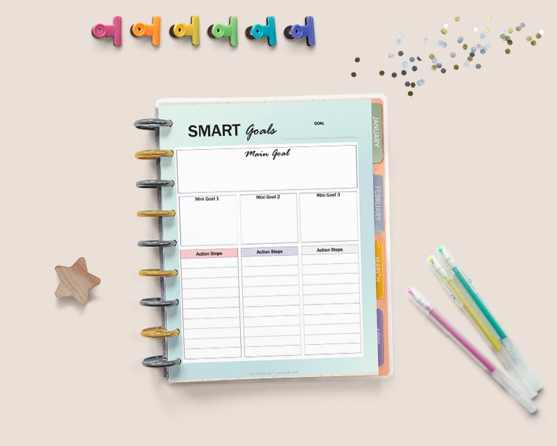 """An open Happy Planner with a page reading """"smart goals"""" with spaces to break each goal into three parts with action steps. There are gel pens, glitter, a wood star, and colorful binder clips around the planner."""