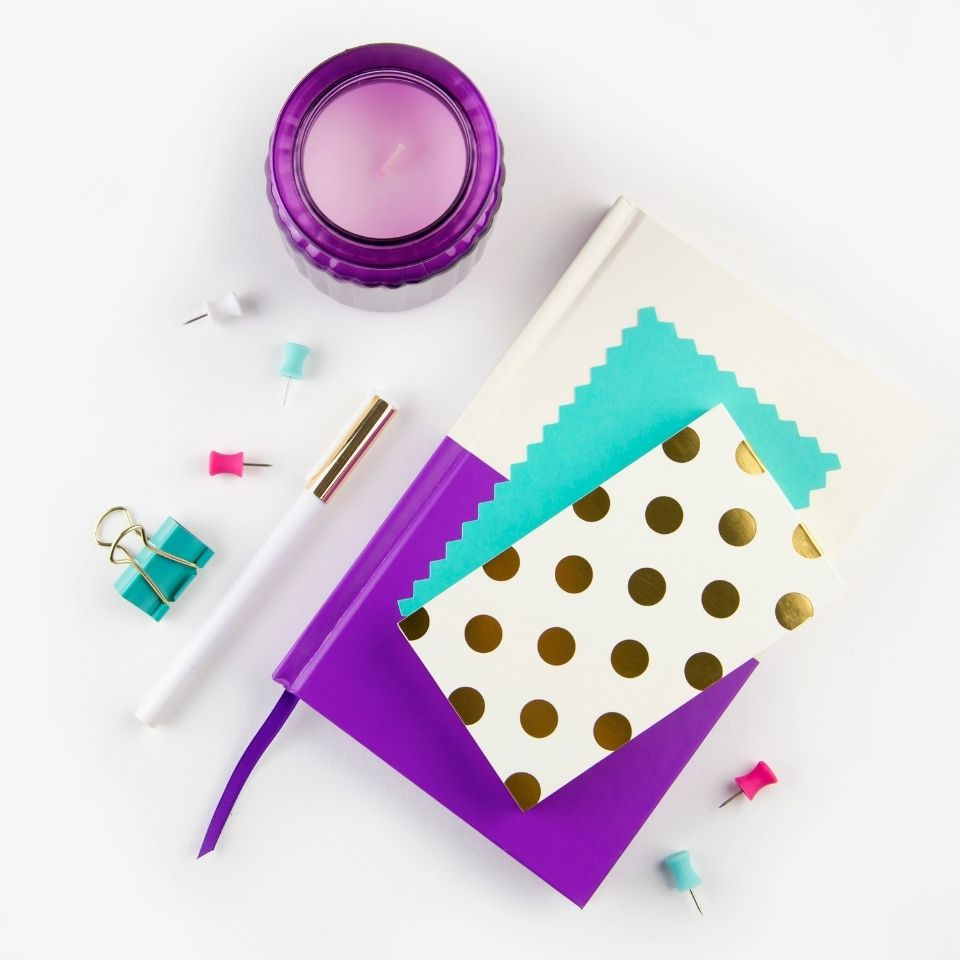Stationary supplies on a white background. A white and purple notebook is in the middle with teal and gold notecards on top. A purple candle is above and to the left. A teal binder clip, pen, and several push pins are around the notebook.