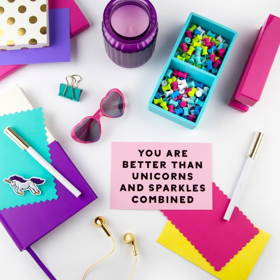 "Teal, purple, and pink stationary supplies with a pair of heart lens pink sunglasses. In the middle is a pink notecard with the message ""you are better than unicorns and sparkles combined"""