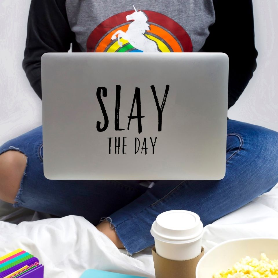"A woman in a rainbow unicorn short working on a laptop with the words ""Slay the day"" on the back. A cup of coffee is visible by her feet. Her face is not visible."