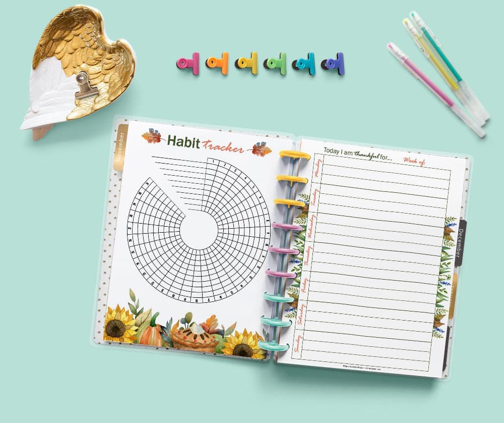 A mockup of an open Happy Planner classic on a light green background showing a habit tracker and a gratitude journal page. There are desk supplies around the planner including colorful binder clips and three gel pens.