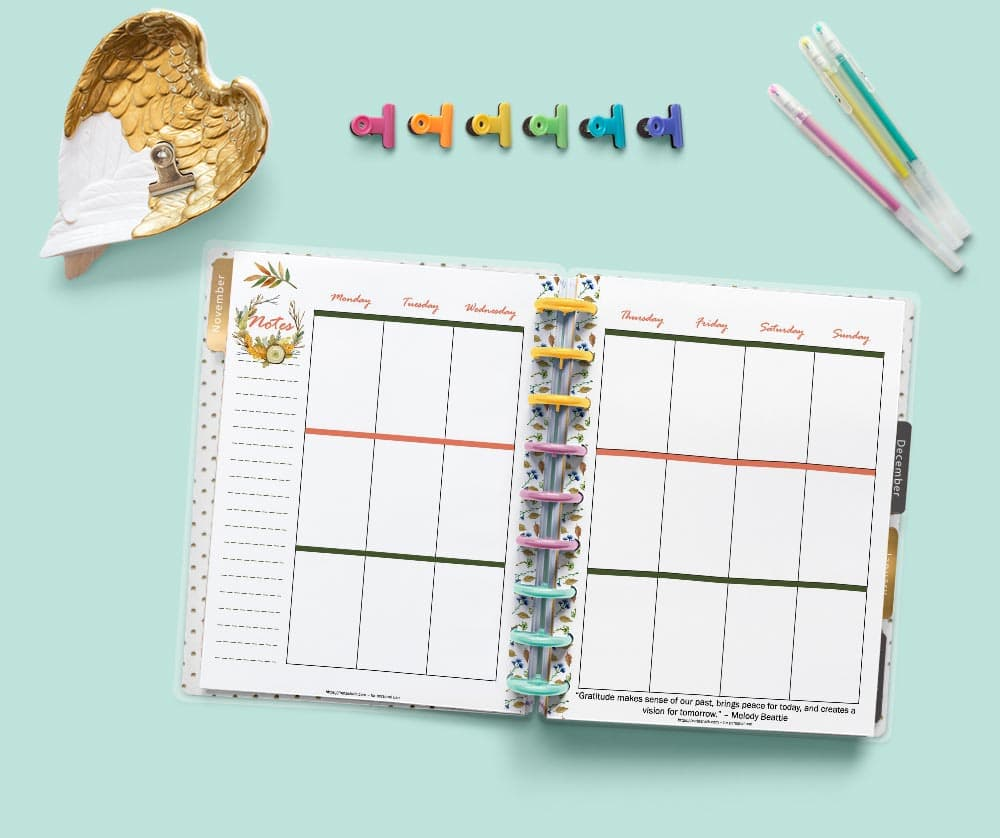 A flatly image of an open Happy Planner with printable vertical weekly layout pages for November. There are desk supplies in the background including binder clips and get pens.