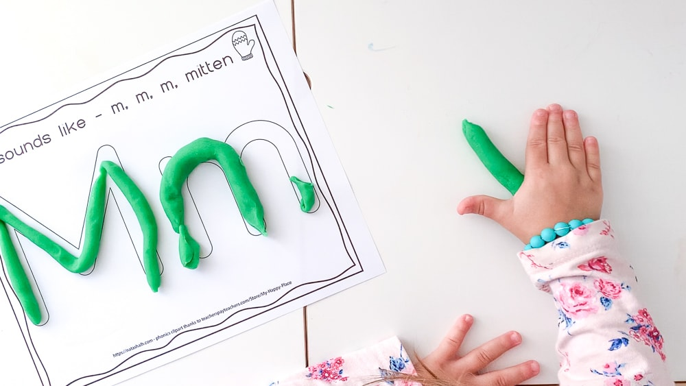 a top down shot of a toddler's hands rolling out green play dough on a white table. Next to her hands is a piece of paper with Mm written in big bubble letters to fill with play dough