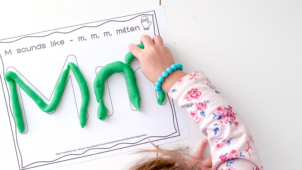 A top down view of a young child with a pink floral shirt on and a blue bracelet placing a piece of green play dough on a letter mat with large bubble letters M and m