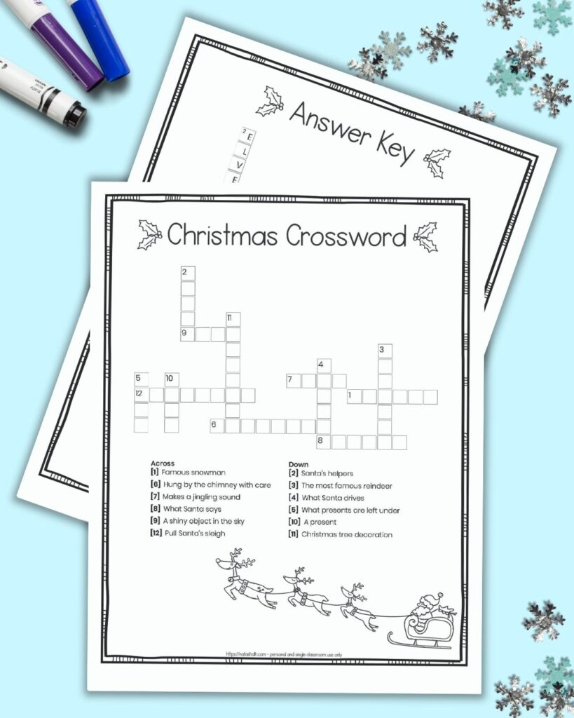 A free printable Christmas crossword puzzle for children with a doodle frame border and black and white image of Santa with his sleigh. The crossword is on a blue background surrounded by children's markers and snowflake shaped confetti. Behind the page with a crossword puzzle a second page is barely visible. It is the puzzle's answer key.
