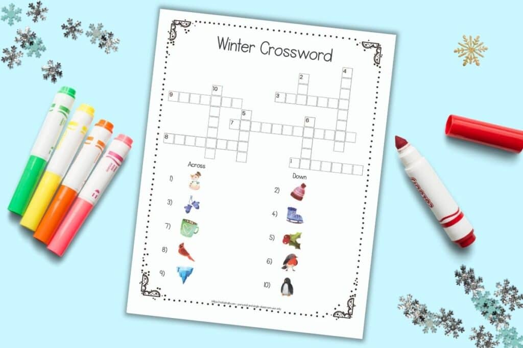 A flatlay of a free printable easy winter crossword with images instead of text-based clues. The page is on a light blue surface with colorful children's markers and snowflake shaped confetti.