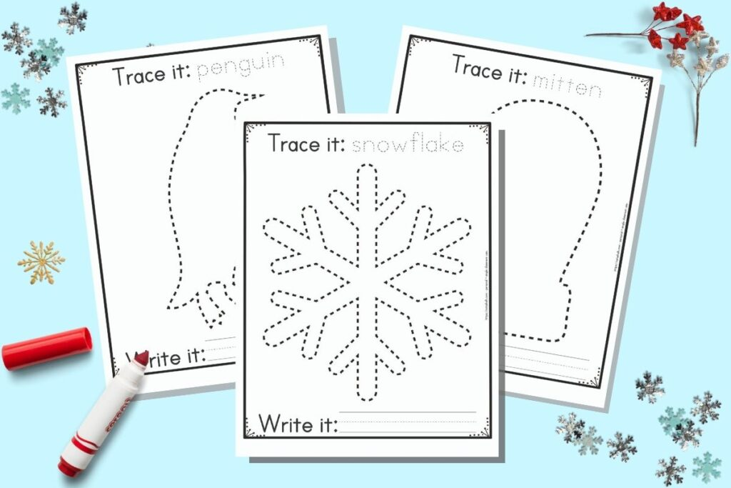 """Three free printable winter themed tracing images for preschoolers and kindergarteners. The front and center page has a dotted snowflake to trace. It has the caption """"Trace it: snowflake"""" on top and """"write it"""" with a blank line for writing below the snowflake. Behind the snowflake are a penguin and a mitten to trace on separate pages. The printables are on a blue background with snowflake confetti and a red child's marker."""