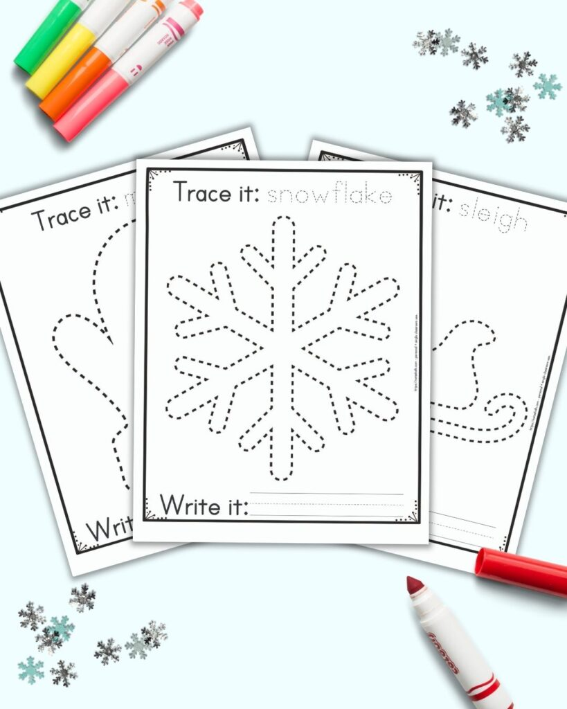 """Three free printable winter themed tracing images for preschoolers and kindergarteners. The front and center page has a dotted snowflake to trace. It has the caption """"Trace it: snowflake"""" on top and """"write it"""" with a blank line for writing below the snowflake. Behind the snowflake are a mitten and a sleigh to trace on separate pages. The printables are on a blue background with snowflake confetti and brightly colored children's markers."""