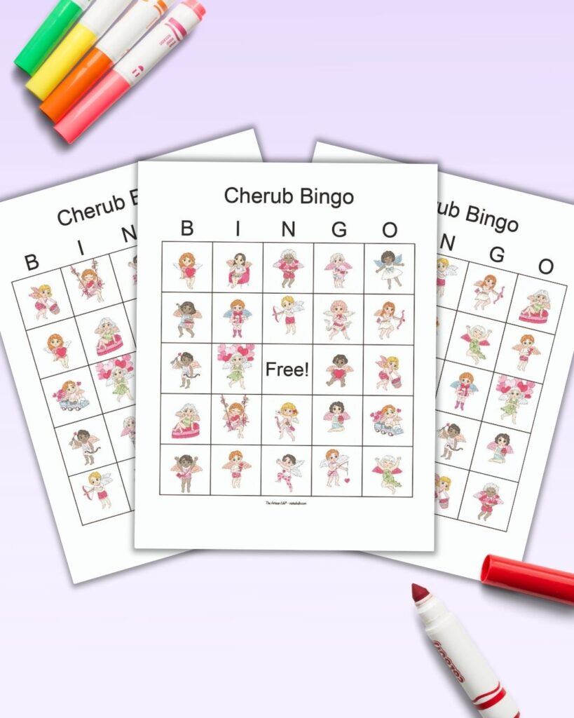A flatlay mockup of three printable picture bingo cards with Valentine's cherubs on a light purple background. There are colorful children's markers on the background with a red open marker on the bottom right corner, as if ready to mark the bingo cards.