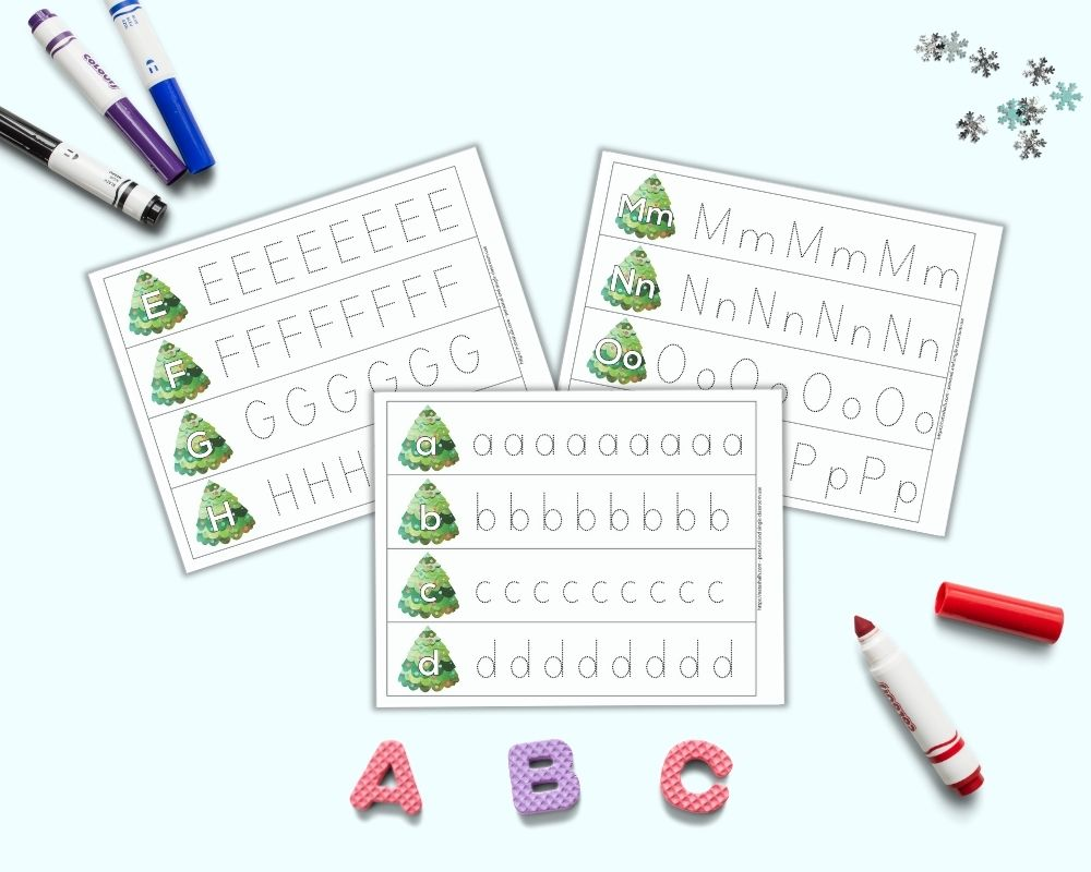 """A preview of three printable alphabet tracing pages for preschoolers. Each page has four rows with one letter per line - a, b, c, etc. A large bubble letter is on a Christmas tree on the left. To the right is a line of dotted letters to trace. The pages are on a light blue surface. Below the pages are foam letters """"A B C."""" There are four colorful children's markers around the printable pages."""