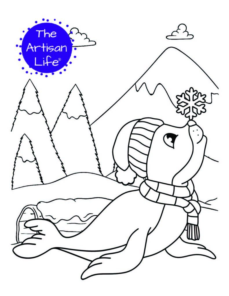 a coloring page with a seal wearing a scarf and hat balancing a snowflake on its nose. Snowy trees and a mountain are in the background
