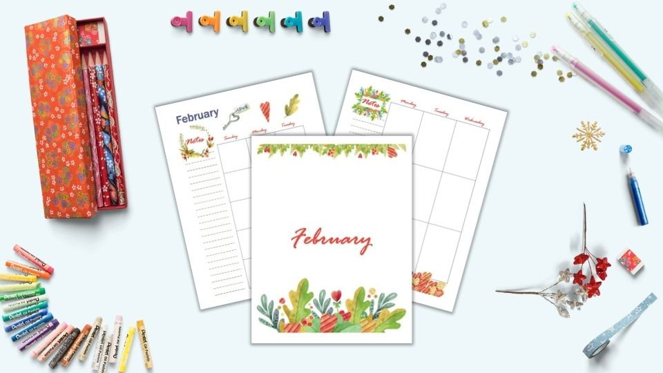 A flatlay of a desk with stationary supplies including colorful binder clips, pencils, gel pens, oil pastels, and blue washi tape. In the center are three printable planner pages for February including a cover page, monthly calendar, and weekly spread
