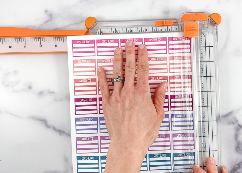 A woman's hand holding a page of printable planer stickers for cutting with a white and orange paper trimer.