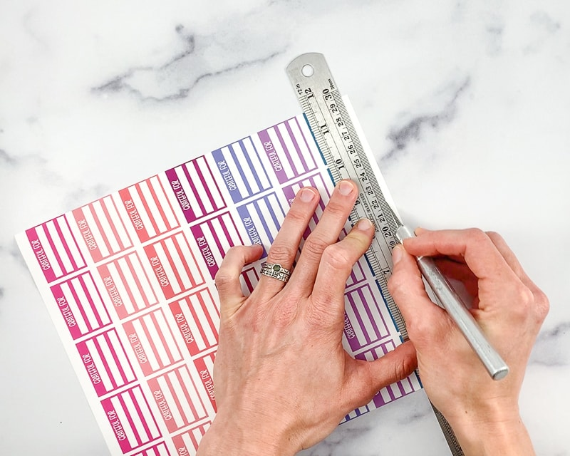 A woman's hands holding a metal ruler and a metal hobby knife against a sheet of printable planner stickers. She is using the hobby knife to cut along the ruler's edge of a row of stickers.