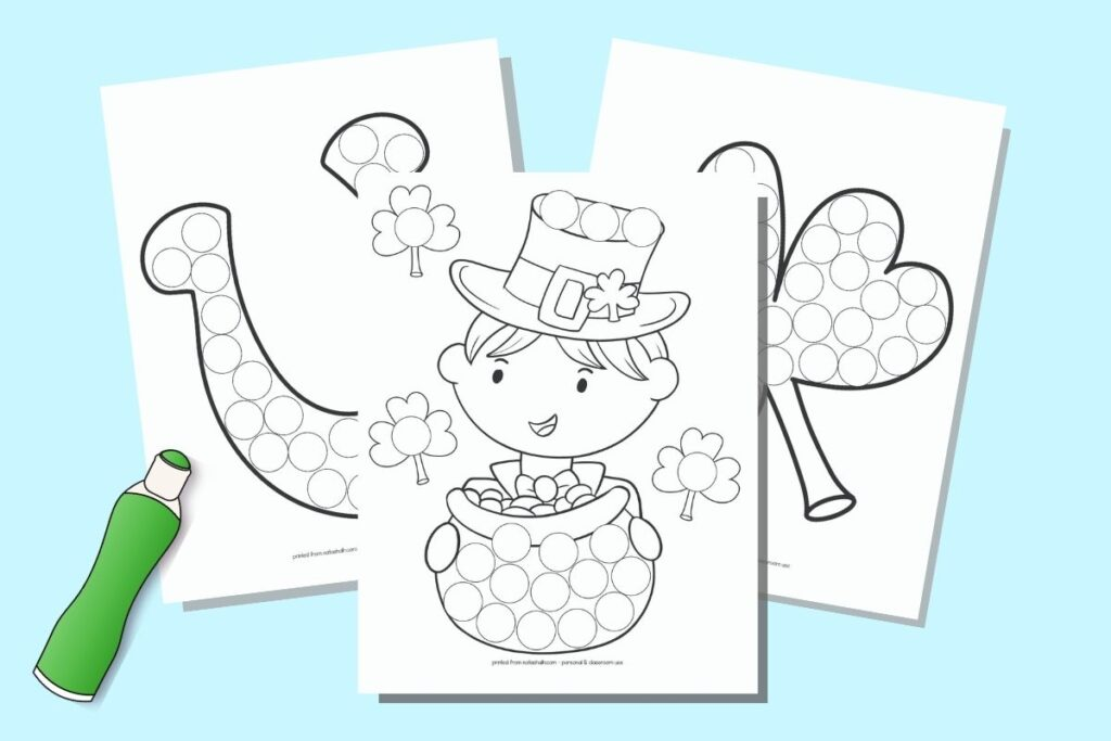 A preview of three printable St. Patrick's Day do a dot coloring pages on a blue background with a drawing of a green bingo dauber marker. The front and center page has a boy with a top hat and pot of gold. Behind are a large shamrock and a lucky horseshoe. Each image is filled with circles to dot in.