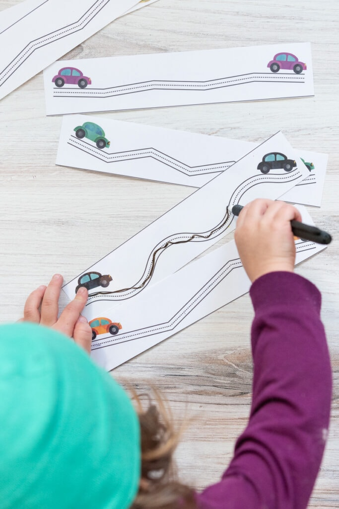 A top down view of a preschooler using a dry erase marker to color in a trace along the lines prewriting practice page with cars on it.