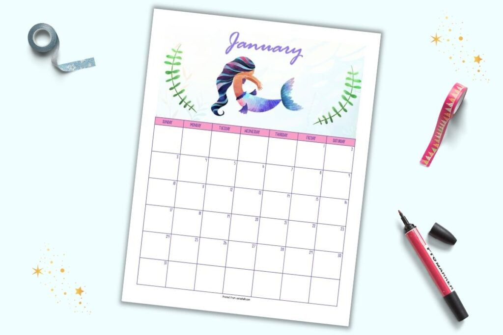 "A printable January 2021 calendar page with a mermaid theme. The mermaid at the top has a purple and pink fin and is centered between two pieces of green seaweed. ""January"" is in script at the top. The page is shown on a blue background with a red marker and rolls of washi tape."