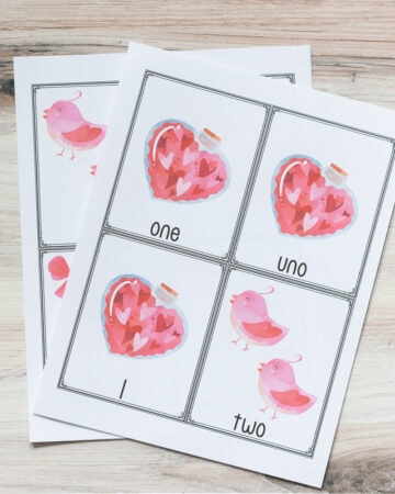 two free printable pages of Valentine's themed counting cards for preschoolers. The top page has three cards for the number 1 with a bottle of hearts and one card for two with two pink birds. The cards are in English, Spanish, and a numeral