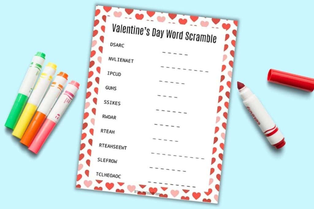 a printable Valentine's Day word scramble for children with a red and pink heart border. The page is on a light blue background with six colorful children's markers. The red marker is open.