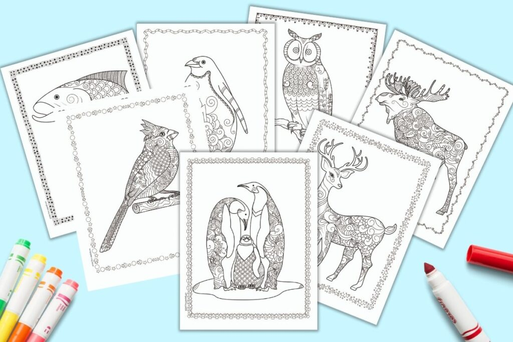 A flatlay preview of 7 printable winter coloring pages for adults. Each page has a winter animal willed with doodles to color. The border of each page has a hand drawn doodle frame. The coloring pages feature a family of penguins, a deer, a moose, an owl, a lone penguin, a cardinal, and a salmon.