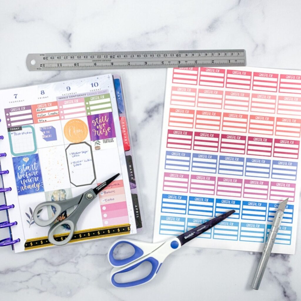 An open Happy Planner next to a page of colorful printed planner stickers. There are also two pairs of scissors, a metal ruler, and a metal hobby knife.