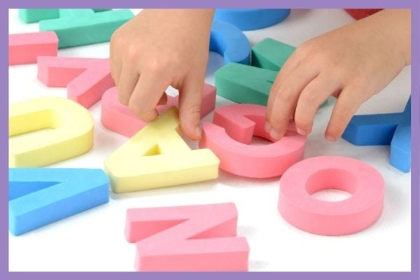 A close up of a child's hands playing with colorful foam letters