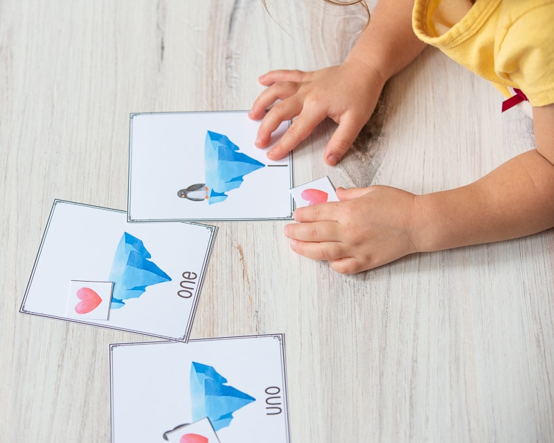 """A child's hand pointing at the number """"1"""" on the bottom of a card with an iceberg and a penguin on it."""