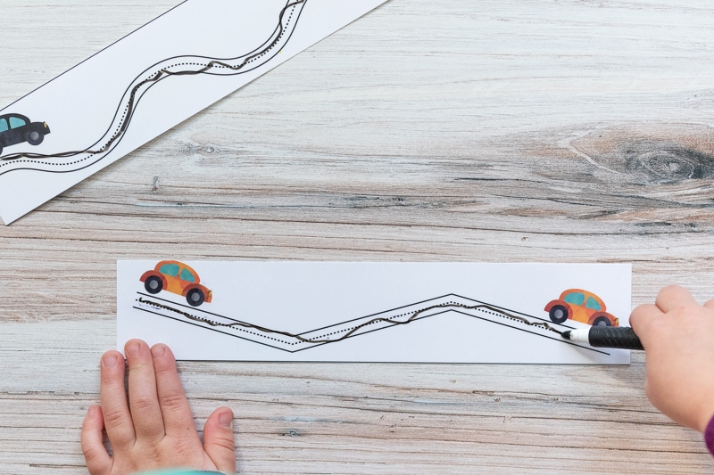 A top down view of a child's hands using a dry erase marker to race inside of a zig-zag path
