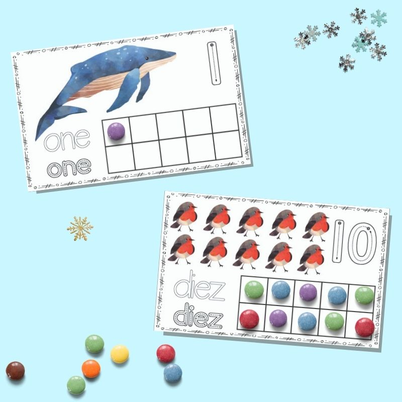 """Two printable winter ten frame cards on a blue background. The upper card has """"one"""" and a single whale with a purple candy in the first spot on the ten frame. The lower card has """"diez"""" with ten red robins and all squares on the ten frame filled in."""