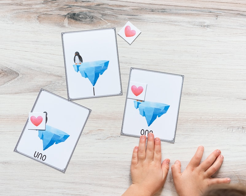 """A young child's hand on a card with """"one"""" and an iceberg on it. There is a red heart card covering a penguin on the card. There are two additional cards on the table. Both have a single card and penguin. One has """"1"""" on the bottom and another has """"uno"""""""
