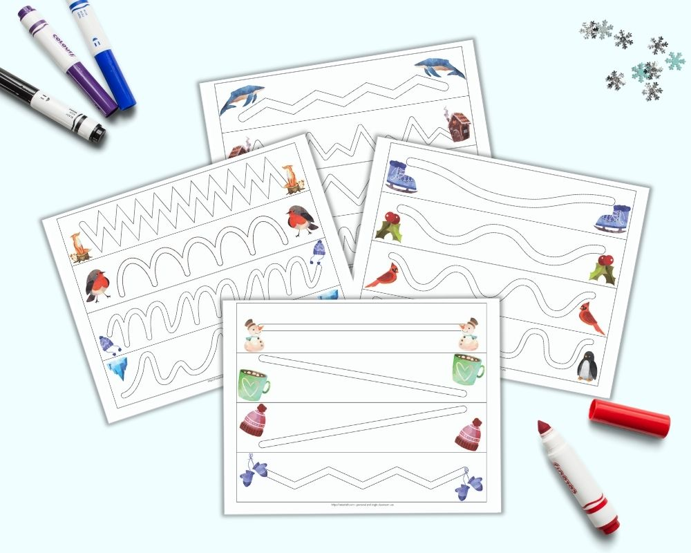a flatlay mockup of four printable trace in the path worksheets for preschoolers. Each page has four paths to trace inside. A watercolor winter-related clip art image is on either side of each path. The pages are on a light blue background with four colorful child's markers and a few pieces of blue and silver snowflake confetti.