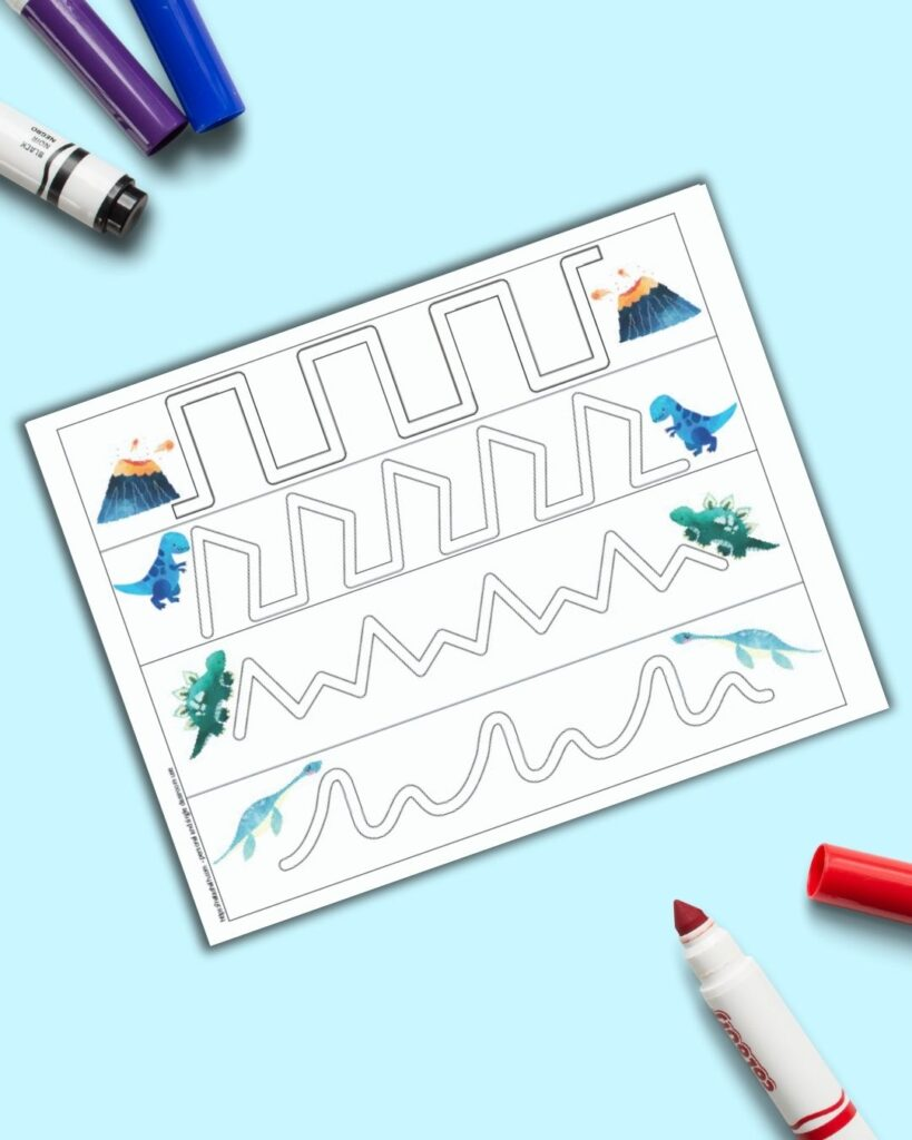 A preview of a dinosaur themed trace in the path fine motor practice page for preschoolers. The page is on a blue surface with colorful children's crayons.