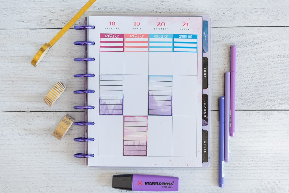 An open Happy Planner Classic with a gratitude journal sticker across the top of each column in a weekly spread page. There are also three full box note stickers. The stickers are full boxes for Happy Planner. Each box has a watercolor landscape background and a translucent white rectangle with seven lines to write on. The planner is on a white wood surface with purple pens, a purple highlighter, and gold washi tape.
