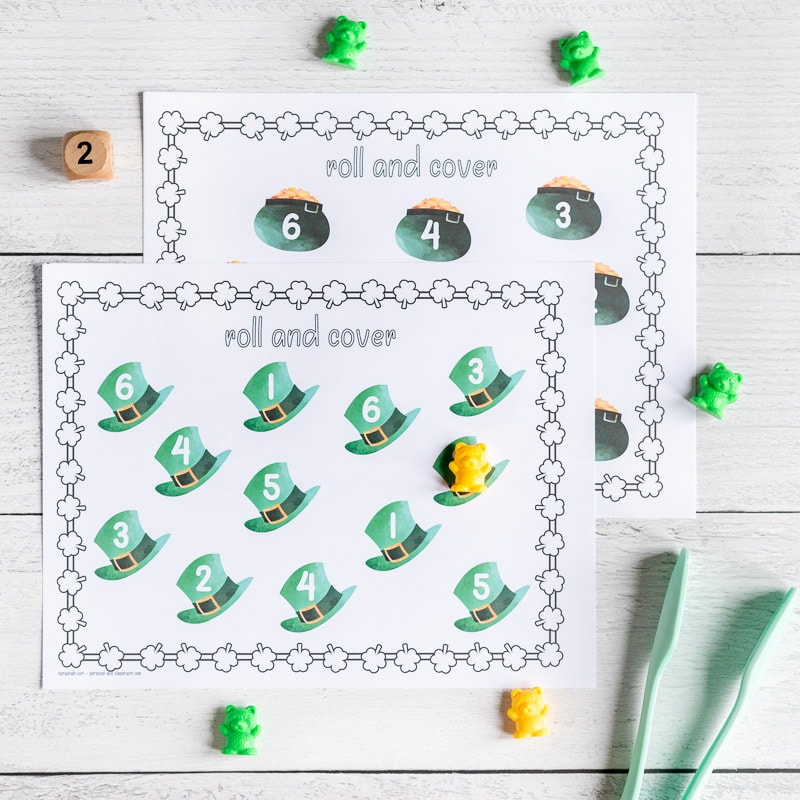 """A printable St. Patrick's Day roll and cover page with 12 green top hats. Each hat has a number 1-6. One hat has a counting bear covering the number. A wood die showing """"2"""" and a paint of tongs are next to the printable page. A second roll and cover page with pots of gold is visible behind the first."""