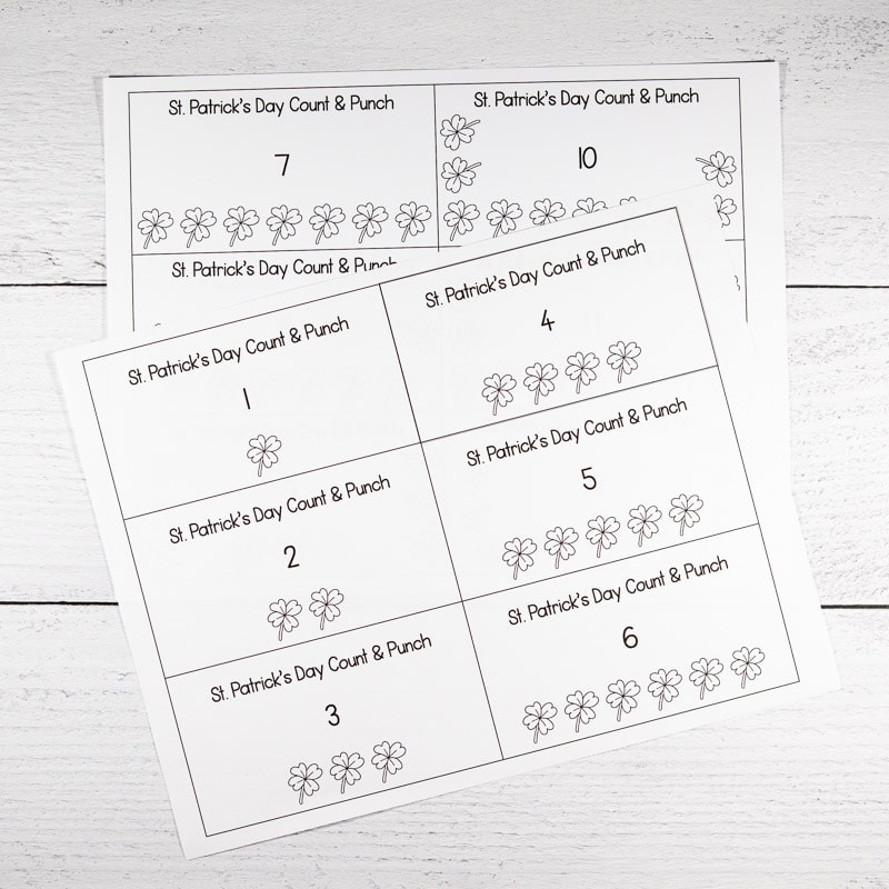 Two pages of printed count and punch cards with a St. Patrick's Day theme on a white wood surface. Each page has 6 cards to cut out and a number of shamrocks 1-12 to punch.