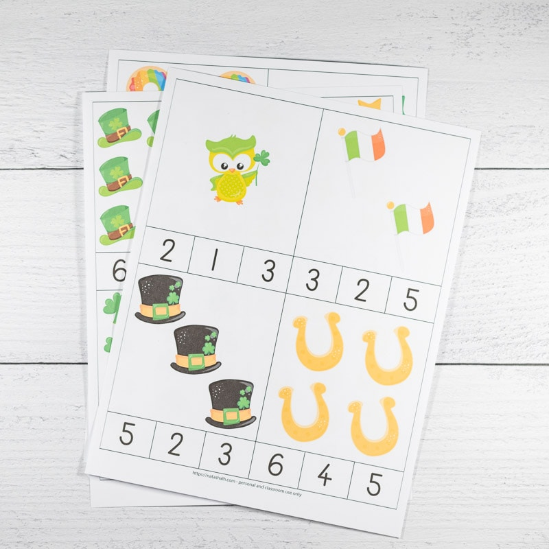 Printable St. Patrick's Day counting clip cards on a white wood surface. The font page is the only one fully visible. It has numbers 1-4 on four cards to cut out. Images include one owl, two Irish flags, three hats, and four horseshoes.