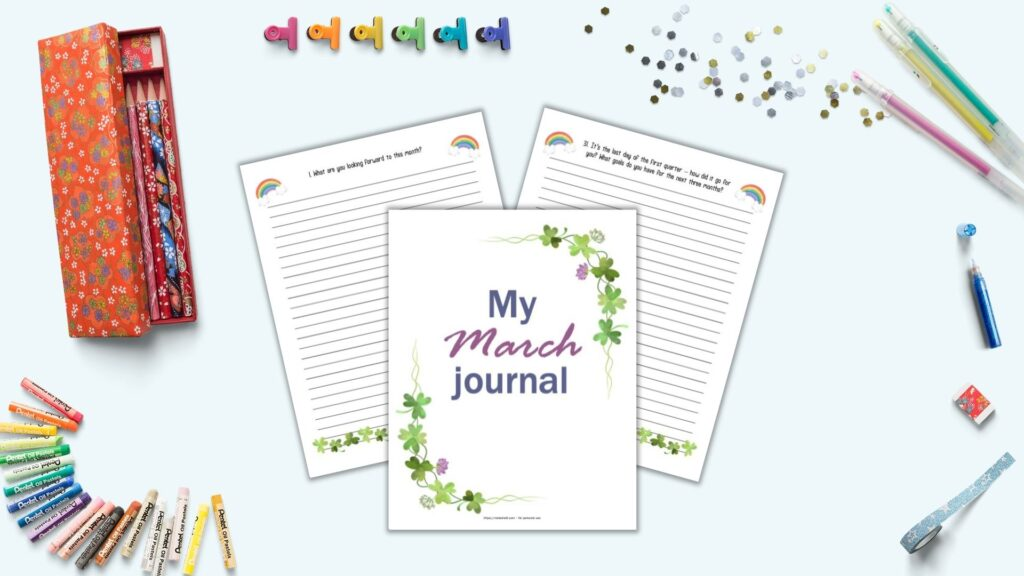 A flatlay mockup with three printable journal pages for March on a  blue surface with office supplies. Supplies include gel pens, colorful binder clips, a Japanese pencil case, washi tape, and oil pastels.