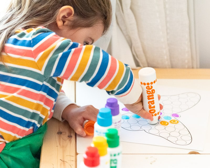 An image of a preschooler in a rainbow striped shirt using an orange dauber style maker to color a butterfly dot marker coloring page